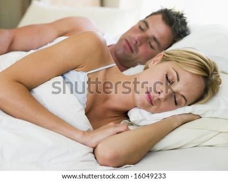 Couple lying in bed sleeping - stock photo