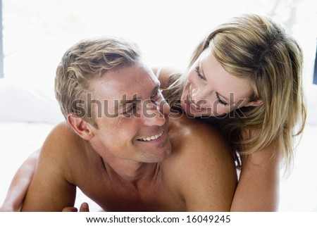 Couple lying in bed smiling - stock photo