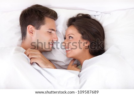 Couple lying in bed smiling at each other - stock photo