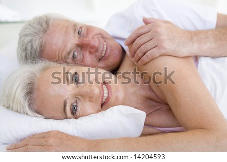 Couple lying in bed together smiling - stock photo