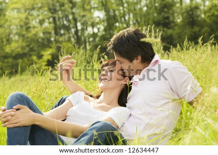 Couple lying in grass, man tickling her girlfriend's nose and smiling - stock photo