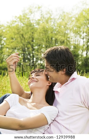 Couple lying in grass, man tickling his girlfriend's nose and smiling - stock photo