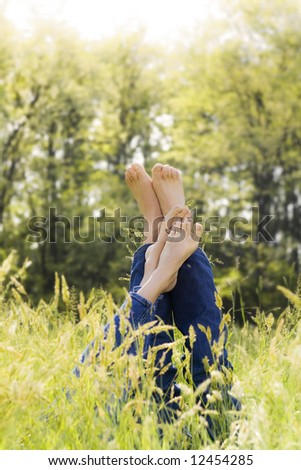 Couple lying in grass stretching their legs up. Copy space - stock photo