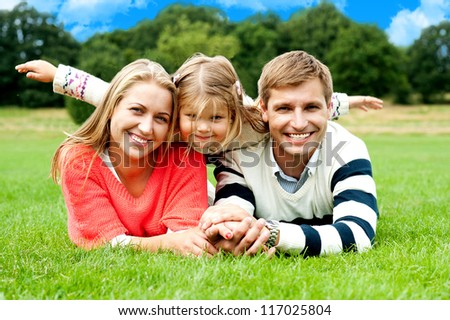 Couple lying in park with their daughter on top. Daughter stretching her hands sideways