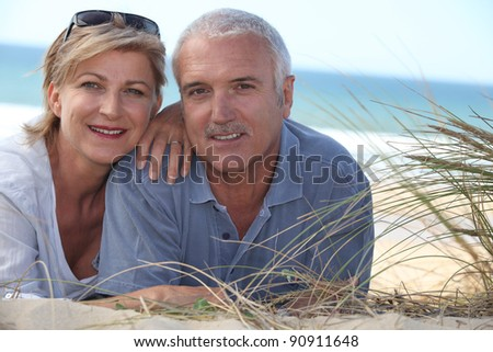 Couple lying in the dunes - stock photo