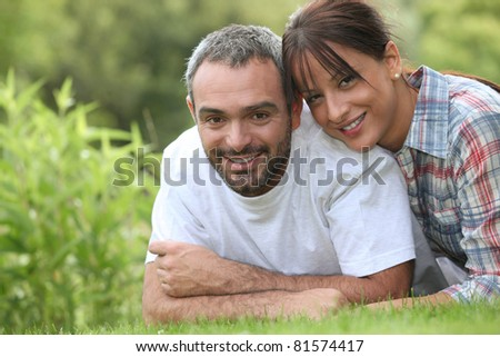 Couple lying in the grass - stock photo