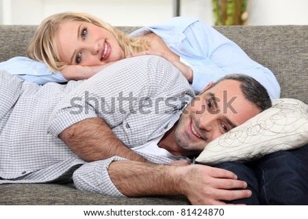 Couple lying on a sofa - stock photo
