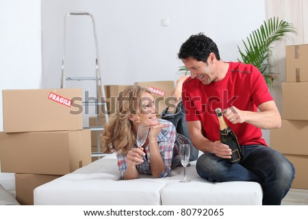 Couple lying on an unmade sofa bed celebrating their new home with champagne - stock photo