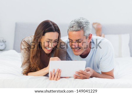 Couple lying on bed using their tablet pc in bedroom