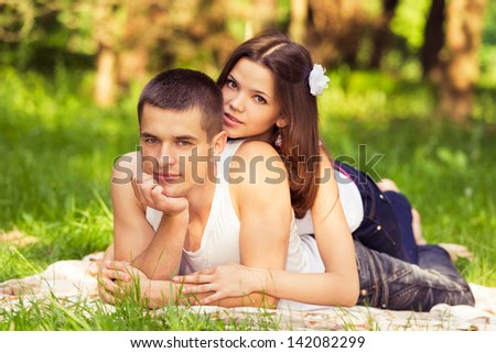 couple lying on blanket at picnic in park - stock photo