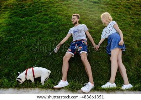 Couple lying on grass, walking with French bulldog in park.