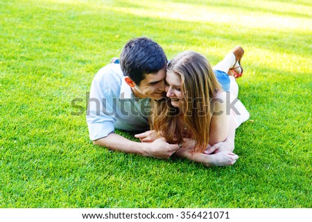 Couple lying on green grass in the park - stock photo