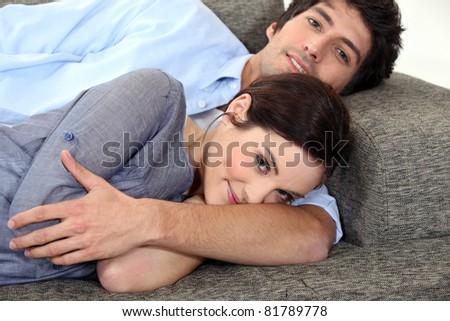 Couple lying on sofa - stock photo