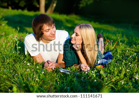 couple lying on the grass in the park. They smile and look at each other - stock photo