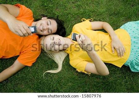 Couple lying on the grass with mobile phones - stock photo