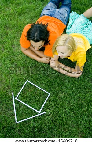 Couple lying on the grass with model house in front of them - stock photo