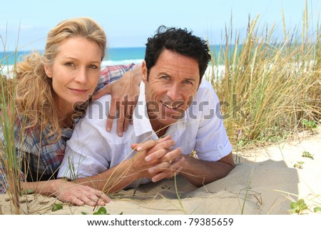 Couple lying on the sand. - stock photo