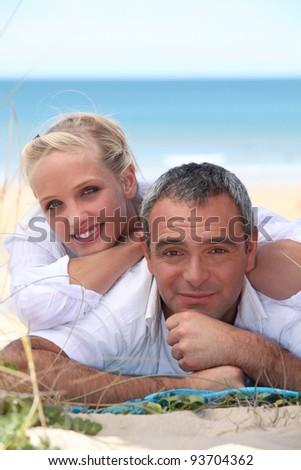 Couple lying on the sand - stock photo
