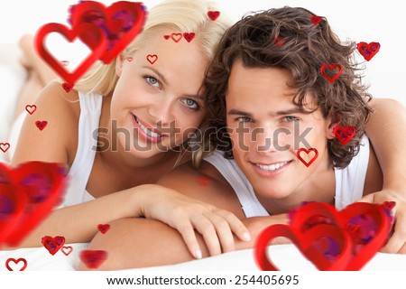 Couple lying on their bed against love heart pattern - stock photo
