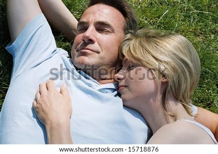 Couple lying outdoors sleeping - stock photo