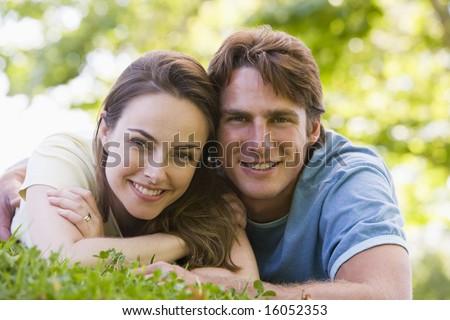 Couple lying outdoors smiling - stock photo