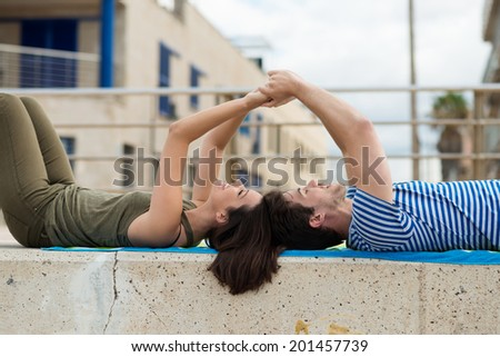 Couple lying relaxing on a cement wall against a white railing in an urban environment holding hands and laughing with enjoyment - stock photo
