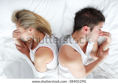 Couple lying separately in bed after having a fight. Marriage trouble - stock photo