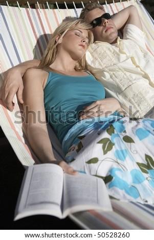 Couple lying together, asleep in hammock - stock photo
