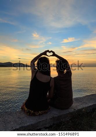 couple makes heart  symbol at dusk - stock photo