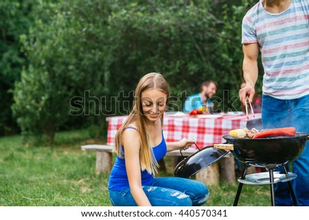 Couple making barbecue and drinking beer together. - stock photo