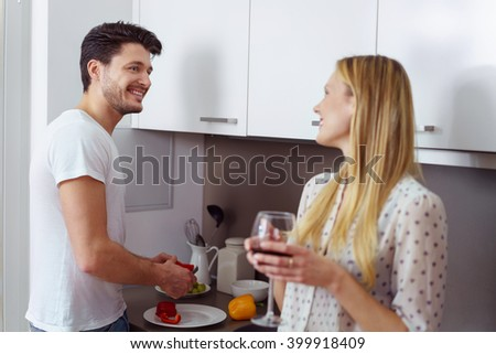 Couple making dinner in the kitchen smiling and laughing as the man prepares the food as the wife enjoys a glass of red wine - stock photo