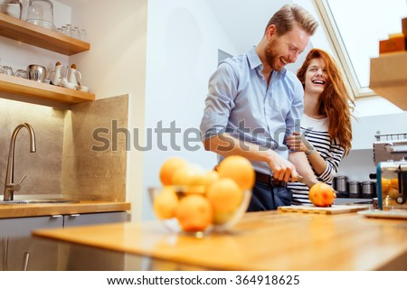 Couple making fresh organic juice in kitchen together - stock photo
