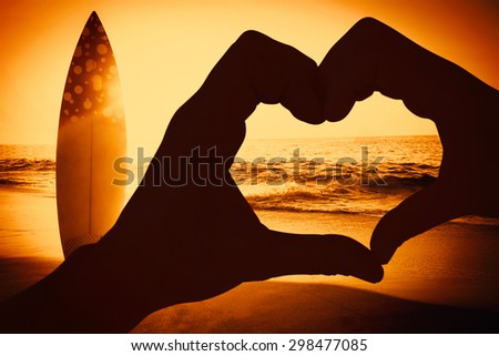 Couple making heart shape with hands against surf board standing on the sand - stock photo