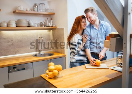 Couple making orange smoothie in kitchen from fresh oranges - stock photo
