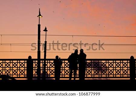 Couple making pictures on the Galata bridge at sunset - stock photo