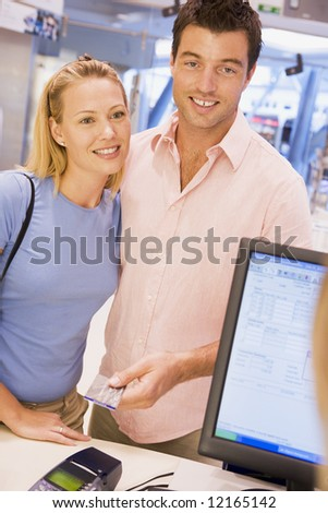 Couple making purchase with credit card in store - stock photo