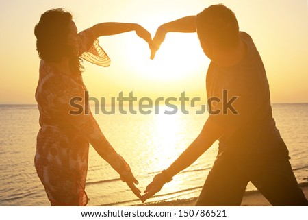 Couple making romantic heart shape at sunrise on the beach - stock photo