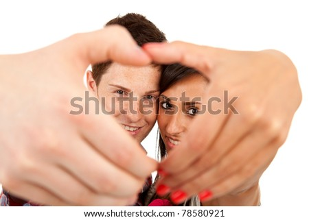 Couple making the shape of a heart with hands and looking through it - stock photo