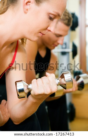 Couple (male / female) having a workout with dumbbells in a gym (woman in front) - stock photo