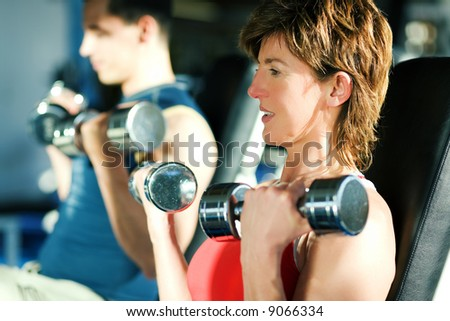 Couple (male / female) lifting dumbbells in a gym; focus on face of the woman