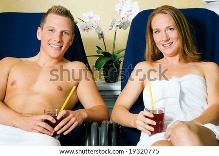 Couple male / female relaxing on beds in a health spa drinking juice - stock photo