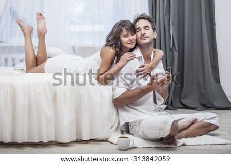Couple man and woman at home in bed with a Cup of coffee. Love, family, relationships, tenderness - stock photo