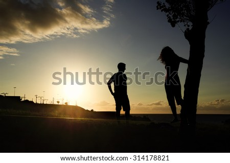 couple man and  woman  balancing in slack line , slacklining , sport in nature at sunset    - stock photo