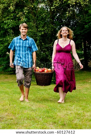 Couple (man and woman) carrying a basket with freshly harvested apples - stock photo