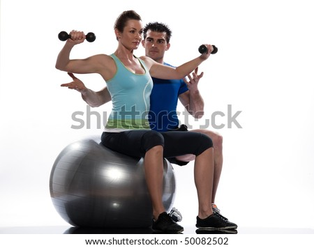 couple, man and woman exercising workout on white background. Seated Swiss Ball Lateral Arm Raise - stock photo