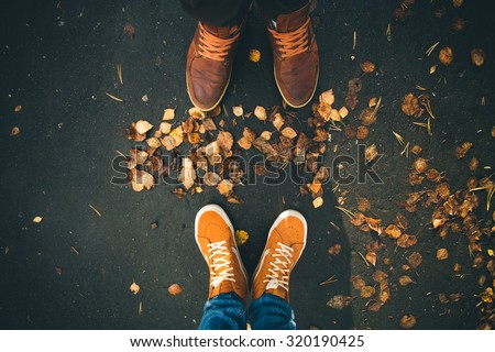 Couple Man and Woman Feet in Love Romantic Outdoor with Autumn leaves on background Lifestyle Fashion concept  - stock photo