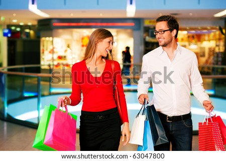 Couple - man and woman - in a shopping mall with colorful bags simply having fun - stock photo