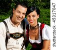 Couple- man and woman - in traditional Bavarian dress, Lederhosen and Dirndl - stock photo
