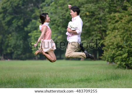 Couple man and woman jump on meadow field at park