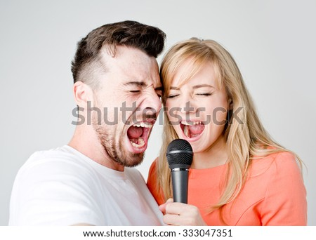 Couple man and woman  shouting or singing into the microphone together on the white background - stock photo
